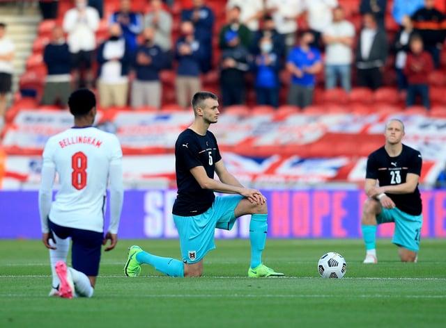 England's Jude Bellingham and Austria's Sasa Kalajdzic take the knee before kick-off