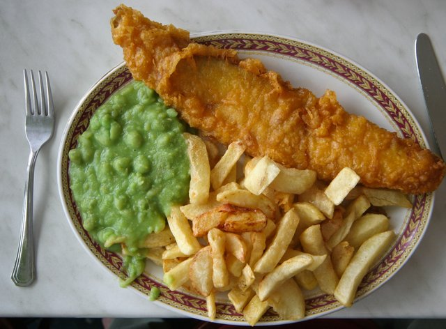 Fish and chips and mushy peas on a plate