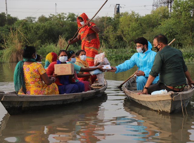 Indian man Himanshu, wearing personal protective suit as a precaution against the coronavirus distributes free aid procured by him to people living in a small island in River Yamuna in New Delhi, India (Amit Sharma/AP)