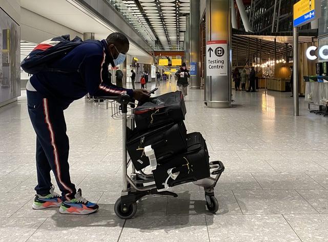 A passenger at Heathrow checks their phone