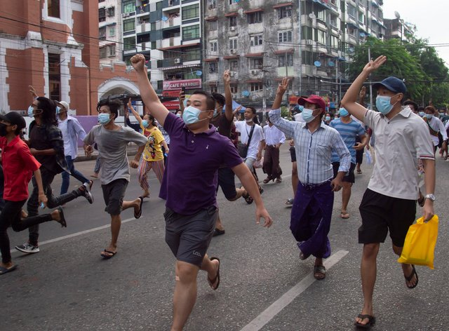 Anti-coup protesters display the three-finger sign of resistance during a flash mob on Thursday, June 3 in Yangon, Myanmar
