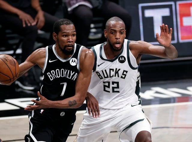 Brooklyn Nets forward Kevin Durant (left) drives to the basket past Milwaukee Bucks forward Khris Middleton