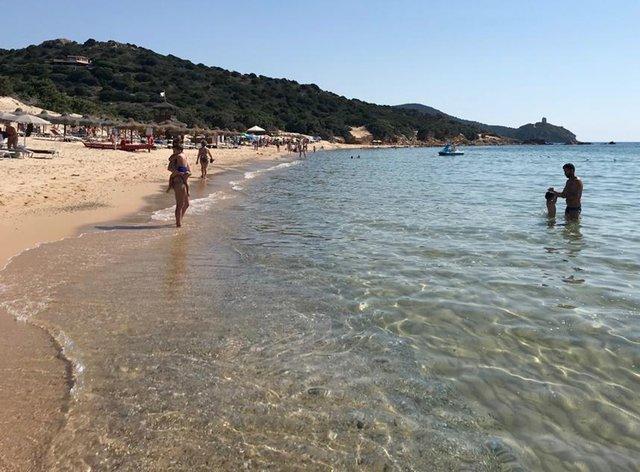 People enjoy one of the beaches of Sardinia