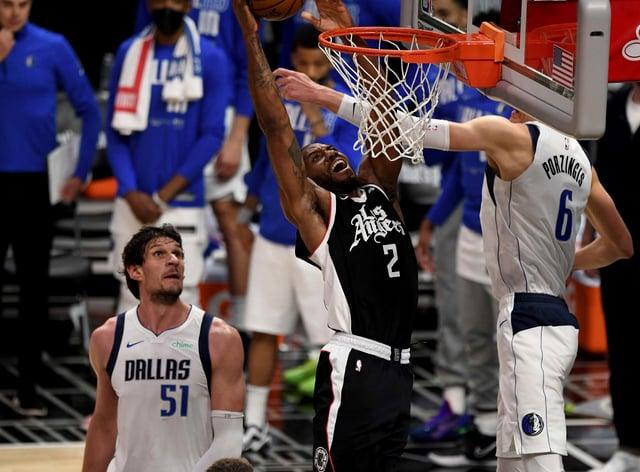 Los Angeles Clippers' Kawhi Leonard (2) slam-dunks over Dallas Mavericks' Kristaps Porzingis