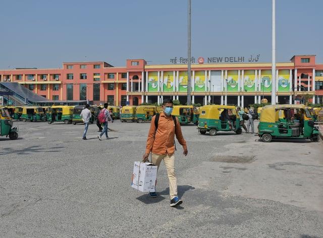 Passengers walk outside the New Delhi railway station in India