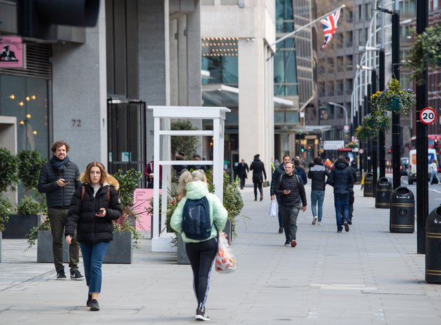 People pass shops and offices on a street in central London