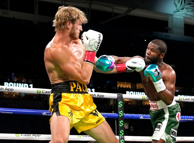 Logan Paul, left, and Floyd Mayweather fight during an exhibition boxing match at Hard Rock Stadium