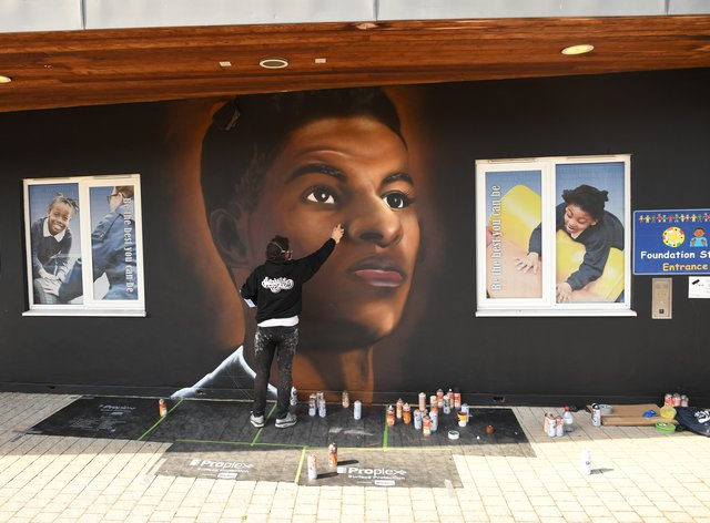Josh from street artists MurWalls paints a mural of footballer Marcus Rashford on the wall of Gainsborough Primary School