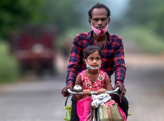 An Indian villager and a child wearing masks ride on a bicycle on the outskirts of Gauhati, India