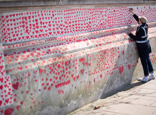 A volunteer adds hearts to the Covid Memorial Wall in London