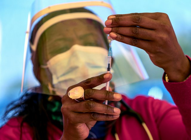 A health worker prepares a dose of the Pfizer coronavirus vaccine