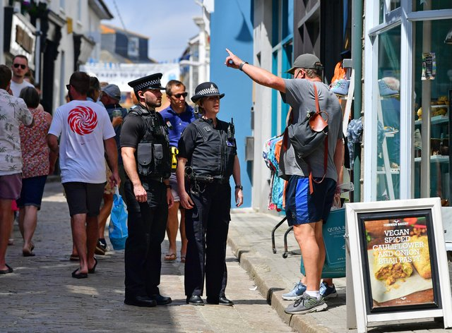 <p>Police officers speak to a member of the public in St Ives</p>