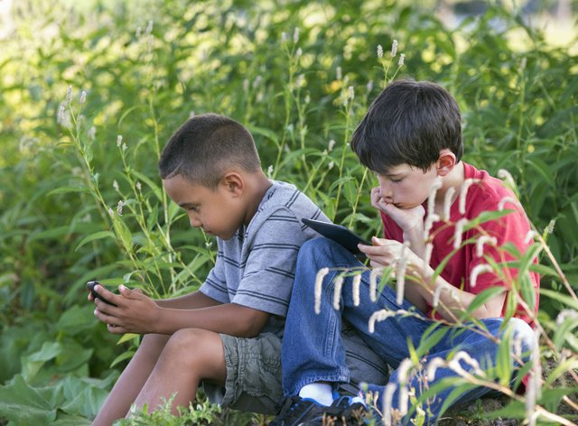 Two boys sitting in a field