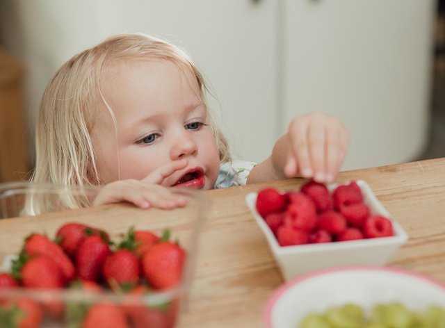 High angle view of a little girl raching over the top of a kicthen counter to grab some raspberries. She is looking for something to eat.