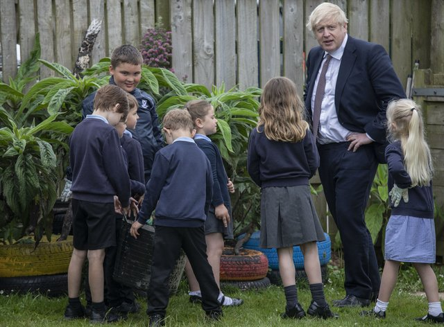 Prime Minister Boris Johnson talks with primary school children in the outdoor spaces at the St Issey C of E Primary school near Wadebridge in Cornwall (Jack Hill/The Times/PA)