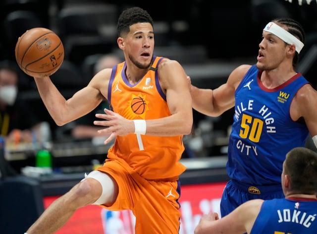 Phoenix Suns guard Devin Booker, left, passes the ball as Denver Nuggets forward Aaron Gordon defends