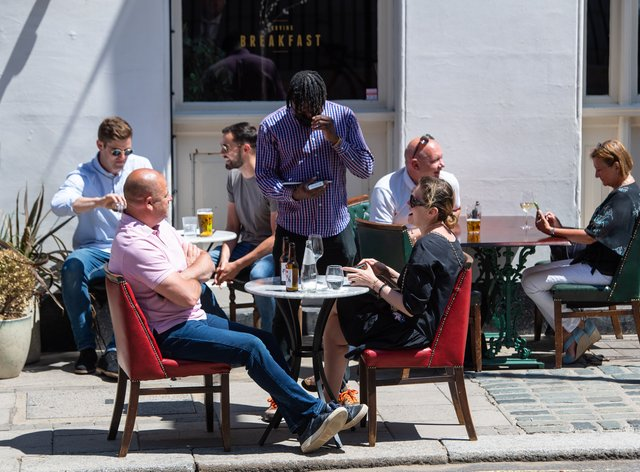 People eat and drink at tables outside a pub