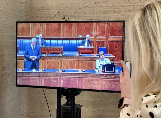 A woman watches a television screen showing DUP leader Edwin Poots (left) in the Stormont Assembly at Parliament Buildings in Belfast pays tribute to Arlene Foster