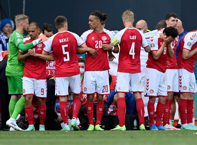 <p>Denmark players make a wall around team-mate Christian Eriksen as he receives treatment on the pitch</p>