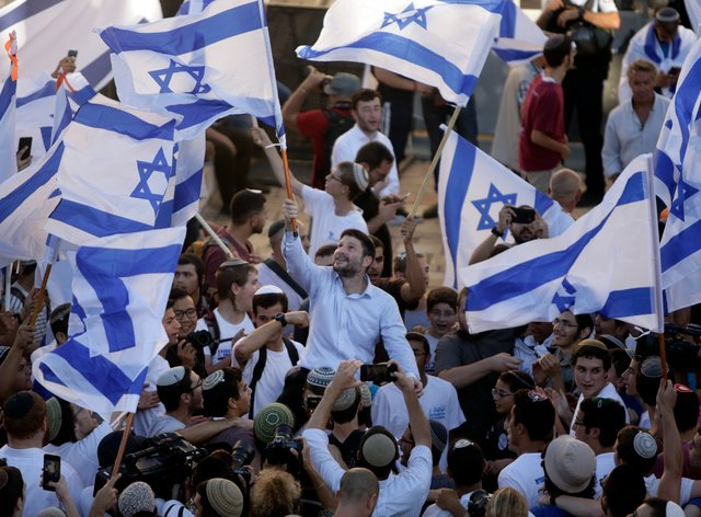 Israeli Knesset member Bezalel Smotrich, centre, waves his country's flag together with other Jewish ultra-nationalists during a march in East Jerusalem on Tuesday