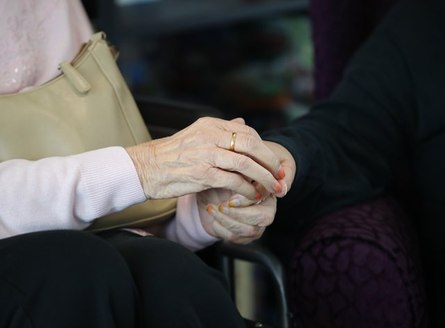 <p>An elderly care home resident holds hands with a visitor</p>