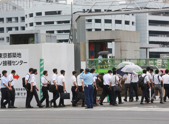 Police officers and firefighters arrive to receive their coronavirus vaccine in Tokyo
