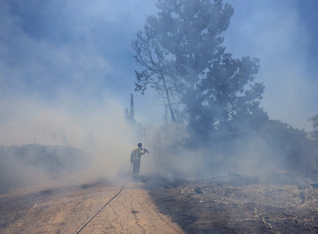 An Israeli firefighter attempts to extinguish a blaze caused by an incendiary balloon launched by Palestinians from the Gaza Strip