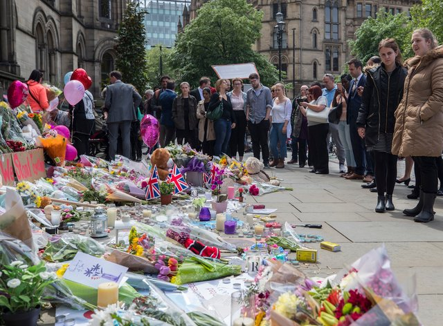 People look at flowers outside the Town Hall in Manchester
