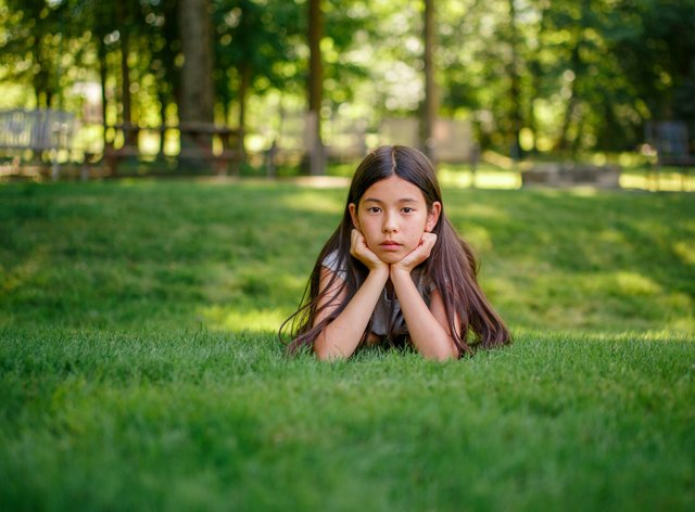 A tween girl lays in the grass with her head propped in her hands