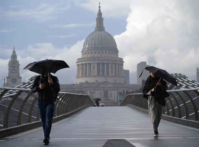 People cross London's Millennium Bridge in the rain