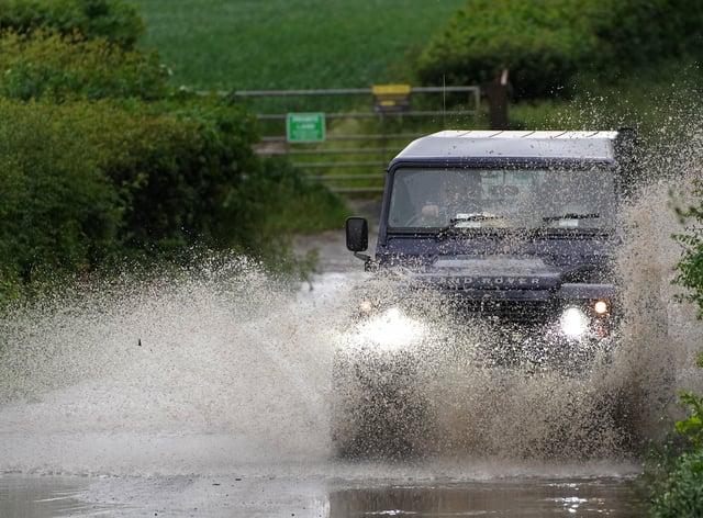 A car drives through a flooded road near Chesham, Buckinghamshire