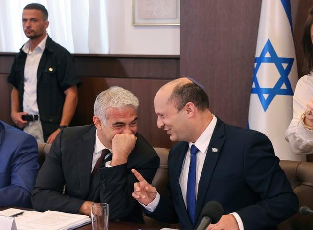 Israeli prime minister Naftali Bennett, right, shares a joke with alternate prime minister and foreign minister Yair Lapid (Emmanuel Dunand/AP)