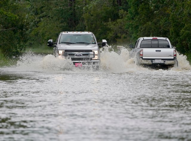 Pickup trucks pass each other on a flooded road in Biloxi, Mississippi