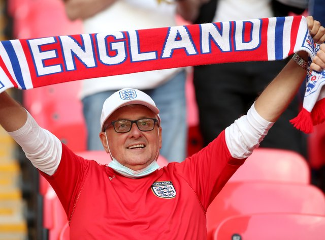 <p>An England fan holding a scarf in the stands at Wembley Stadium</p>