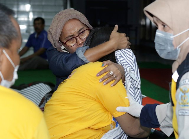 A relative embraces a survivor of the sinking ferry KMP Yunice at an evacuation point in Banyuwangi, East Java, Indonesia