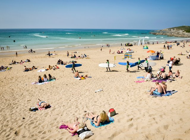 People relax in the sun at Fistral Beach