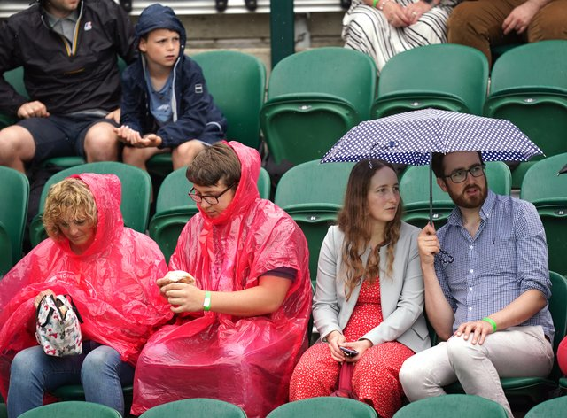 <p>Spectators shelter from the rain on day six of Wimbledon</p>