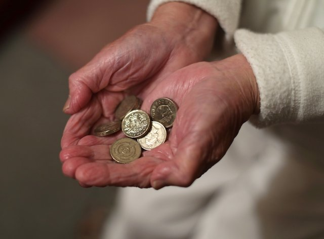 Elderly person holding coins