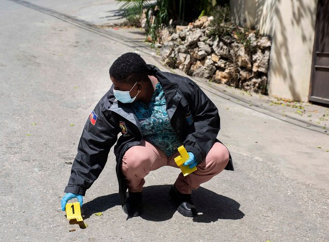 An investigator places an evidence marker next to a bullet casing (Joseph Odelyn/AP)