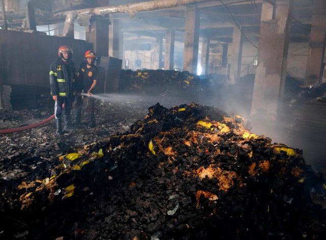 Firefighters work to douse a fire inside a food and beverage factory in Rupganj, outside Dhaka, Bangladesh (Mahmud Hossain Opu/AP)