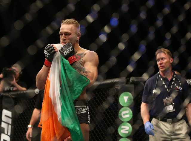 Ireland's Conor McGregor hold the Irish flag