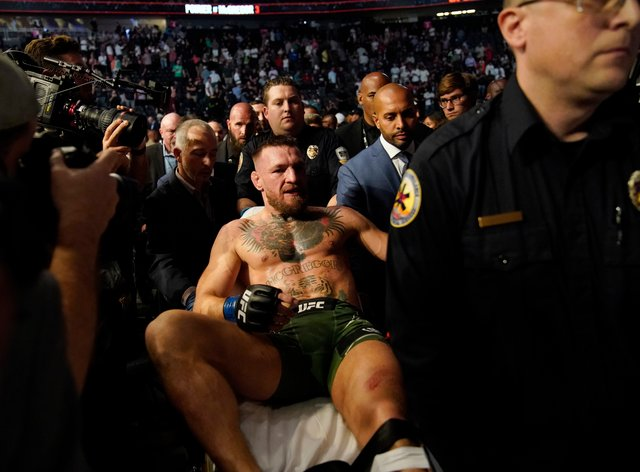 Conor McGregor leaves the arena on a stretcher after suffering a suspected broken leg.