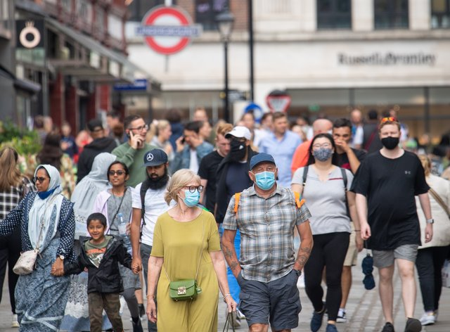 People wearing face masks among crowds of pedestrians in Covent Garden, London