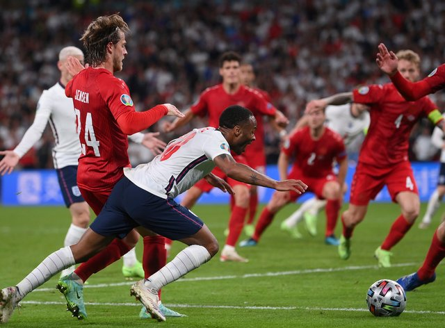 Raheem Sterling goes down after a challenge in the box, winning England a penalty in the Euro 2020 semi-final against Denmark
