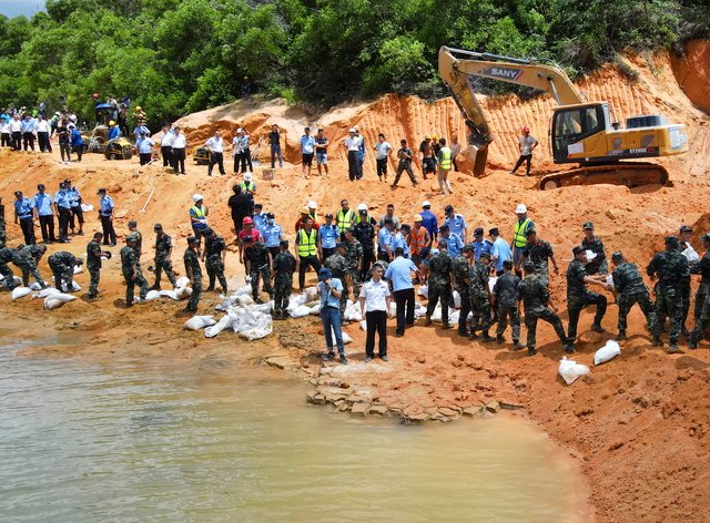 Rescuers work to build an embankment at the site of a flooded tunnel in China's Guangdong Province