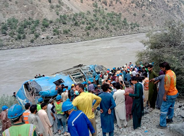Local residents and rescue workers gather at the crash site