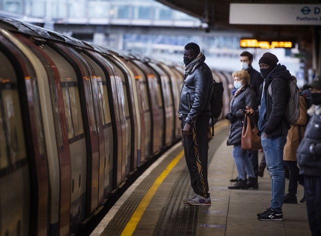 Commuters getting on a Jubilee Line Underground train at Canning Town station during the morning rush hour in London, as England's third national lockdown to curb the spread of coronavirus continues (Victoria Jones/PA)