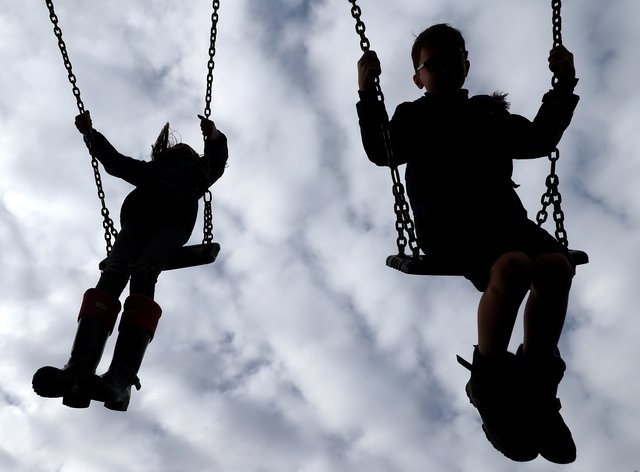 Children enjoy playing on swings in a park
