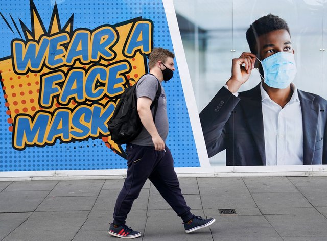 A member of the public in Nottingham walks past a notice encouraging the wearing of face masks