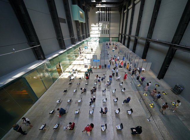 People waiting for their vaccinations at an NHS pop-up vaccination centre at the Tate Modern art gallery in London (Kirsty O'Connor/PA)